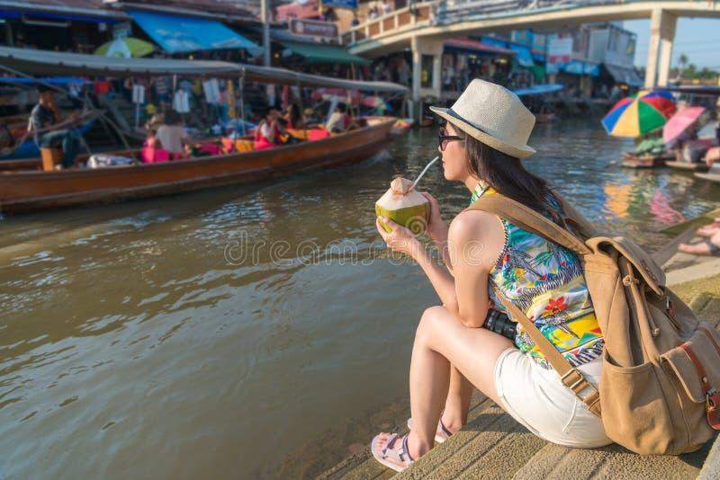 La donna si siede sulla sponda del fiume e sulla tenuta della noce di cocco fotografie stock