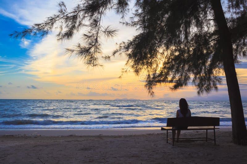 La donna si siede sulle sedie sotto l'albero sulla spiaggia immagini stock
