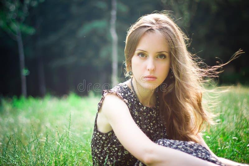 La donna si siede in una foresta fotografie stock libere da diritti