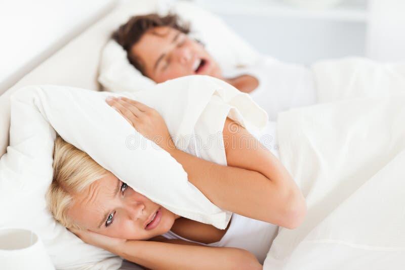 La donna si sveglia dal suo marito che russa fotografia stock libera da diritti