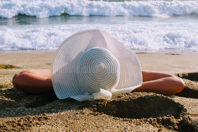 La donna si trova sulla sabbia contro lo sfondo della spuma del mare in un cappello bianco con l'ampio bordo fotografie stock