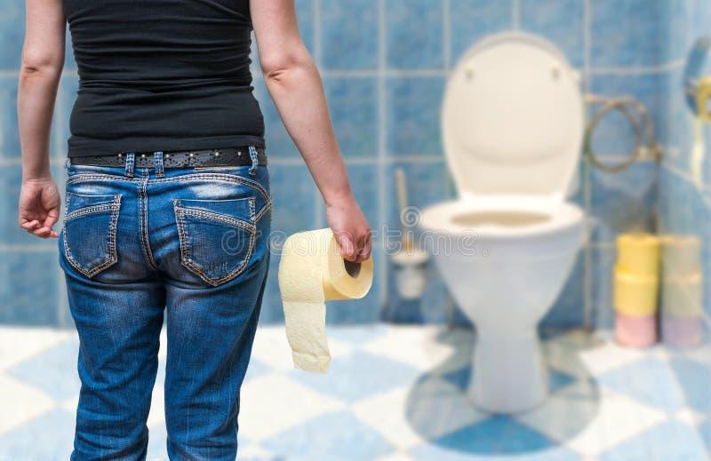 La donna soffre da diarrea giudica la carta igienica disponibila nella toilette fotografie stock