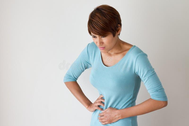 La donna soffre da dolore di mestruazione o dal dolore di stomaco immagini stock