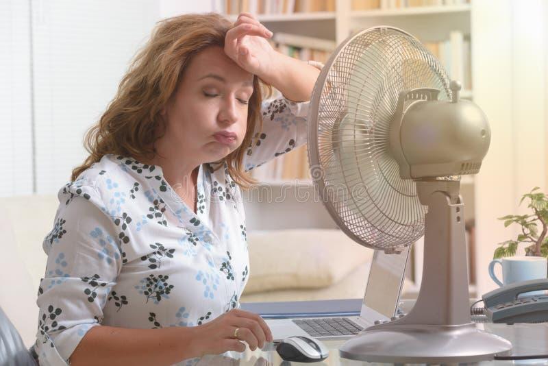 La donna soffre dal calore nell'ufficio o a casa fotografia stock libera da diritti