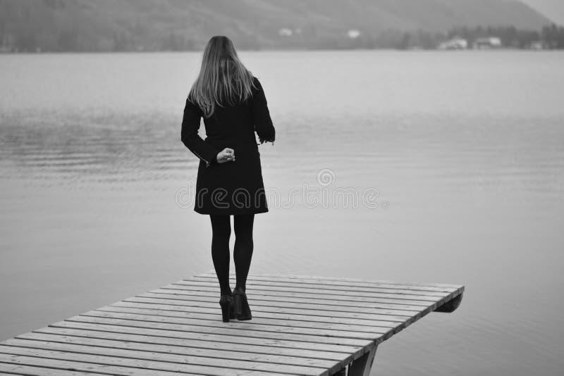 la donna sola esamina tristemente il lago nell'inverno fotografie stock libere da diritti
