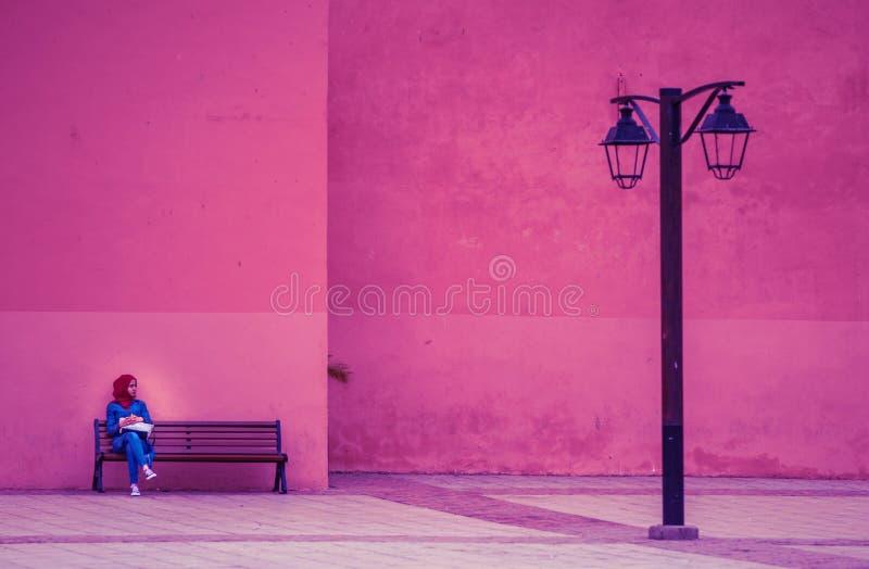 La donna sola povera si siede in via della città con il vestito variopinto tradizionale dalla mussola, Marrakesh, Marocco immagine stock libera da diritti