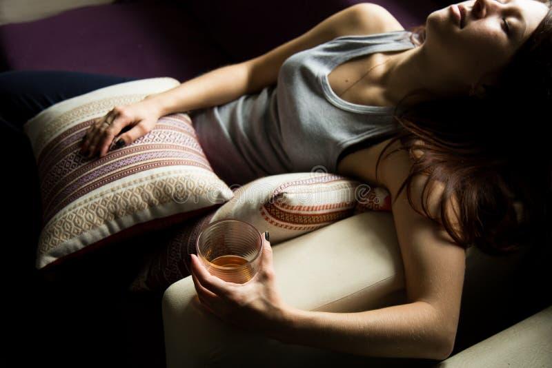 La donna sola triste beve l'alcool nello scuro Vetro nel fuoco tagliente Alcolismo femminile fotografia stock libera da diritti