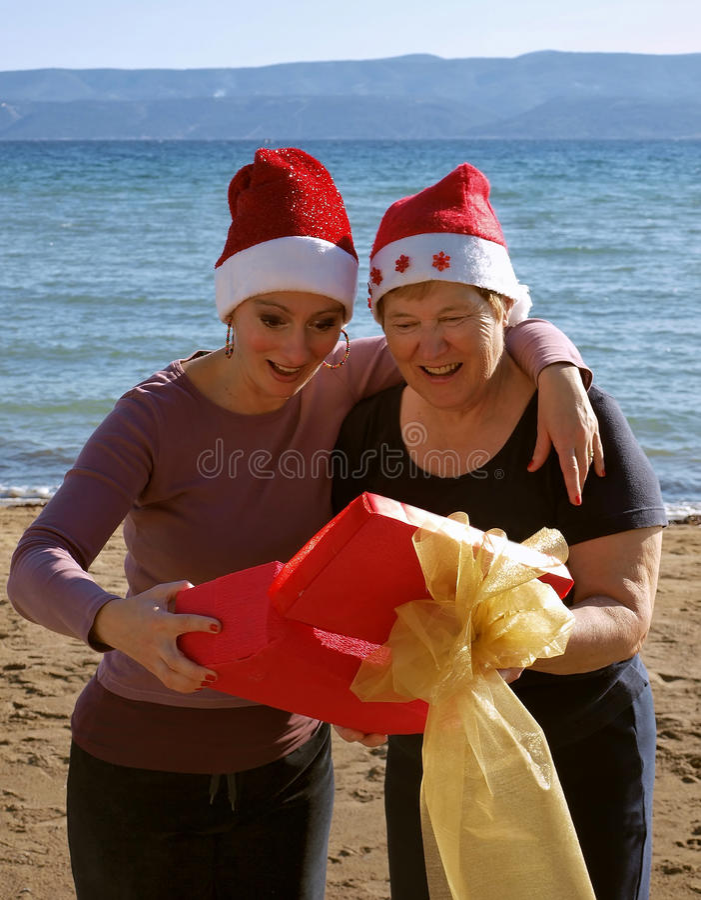 La donna sorpresa apre un regalo di natale fotografia stock