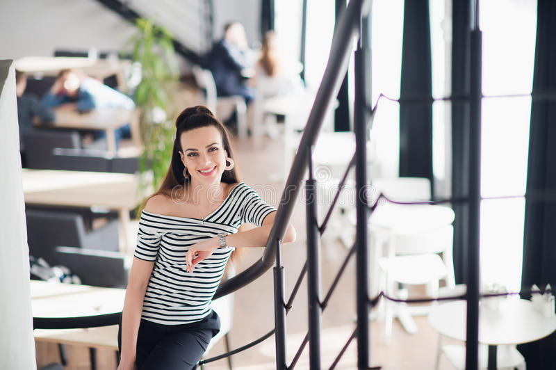 La donna sorridente attraente con trucco naturale sta stando in un caffè e sta esaminando la macchina fotografica fotografia stock libera da diritti