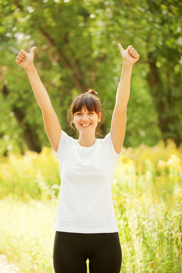 La donna sorridente che mostra i pollici aumenta il segno fotografie stock libere da diritti