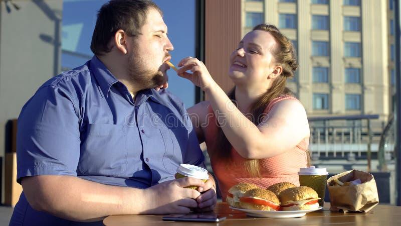 La donna sorridente che tratta le patate fritte del ragazzo, coppie grasse data, alimento non sano fotografia stock
