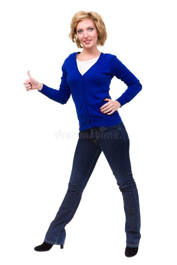 La donna sorridente con i pollici aumenta la posizione di gesto immagine stock