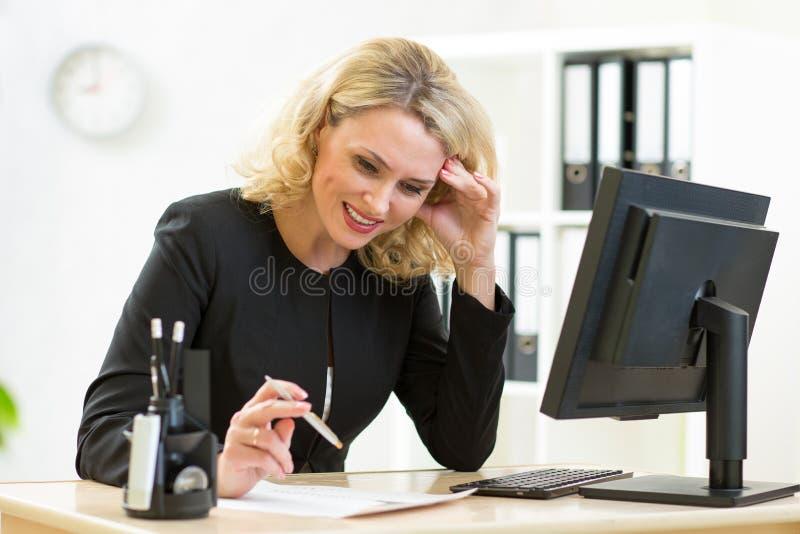 La donna sorridente di affari esamina la seduta del documento immagini stock libere da diritti