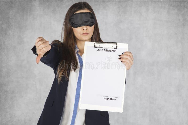 La donna sorridente di affari mostra il pollice verso l'alto, bendato gli occhi fotografia stock