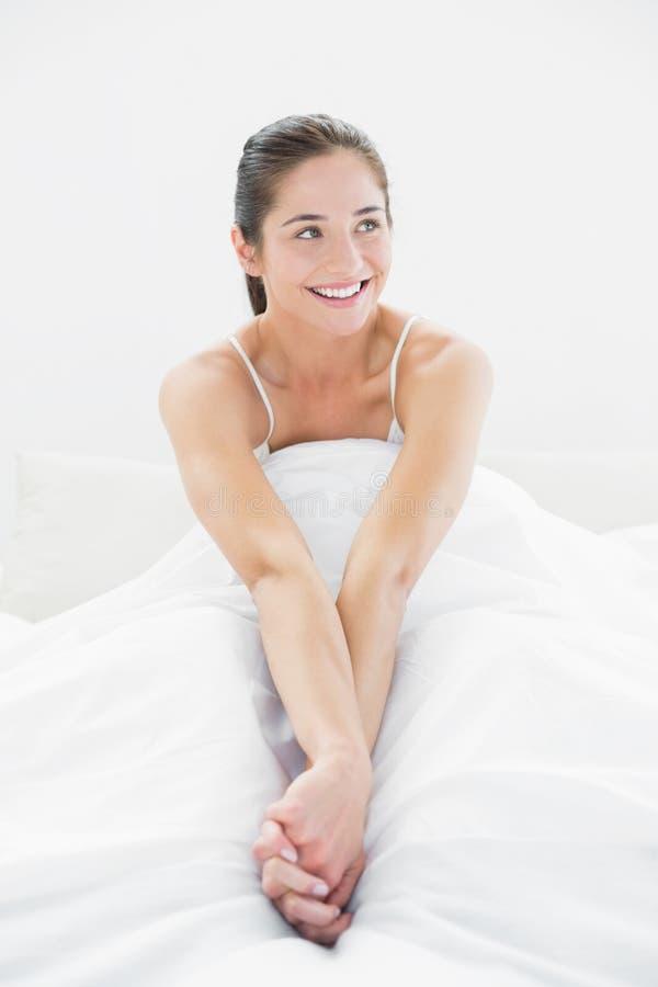 La donna sorridente distoglie lo sguardo a letto fotografie stock