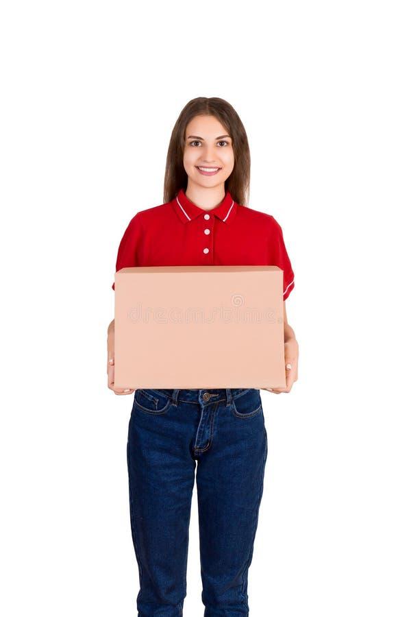 La donna sorridente felice attraente della consegna sta giudicando una scatola di cartone isolata su fondo bianco fotografie stock libere da diritti