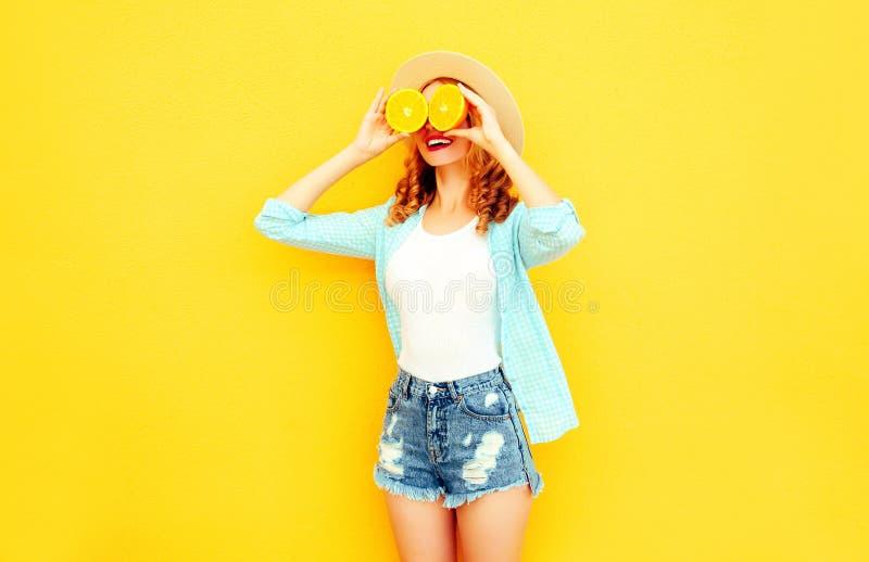 La donna sorridente felice del ritratto dell'estate che tiene nelle sue fette delle mani di arancia che nascondono i suoi occhi i fotografie stock libere da diritti