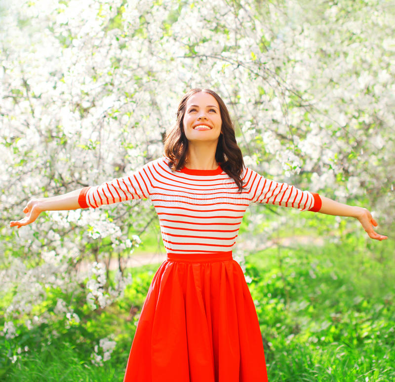 La donna sorridente graziosa felice che gode dell'odore fiorisce durante la molla fotografie stock