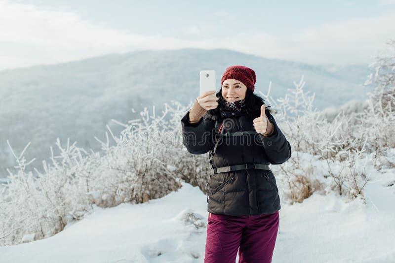 La donna sorridente ha vestito caldo prendendo un selfie in un paese nevoso fotografie stock libere da diritti