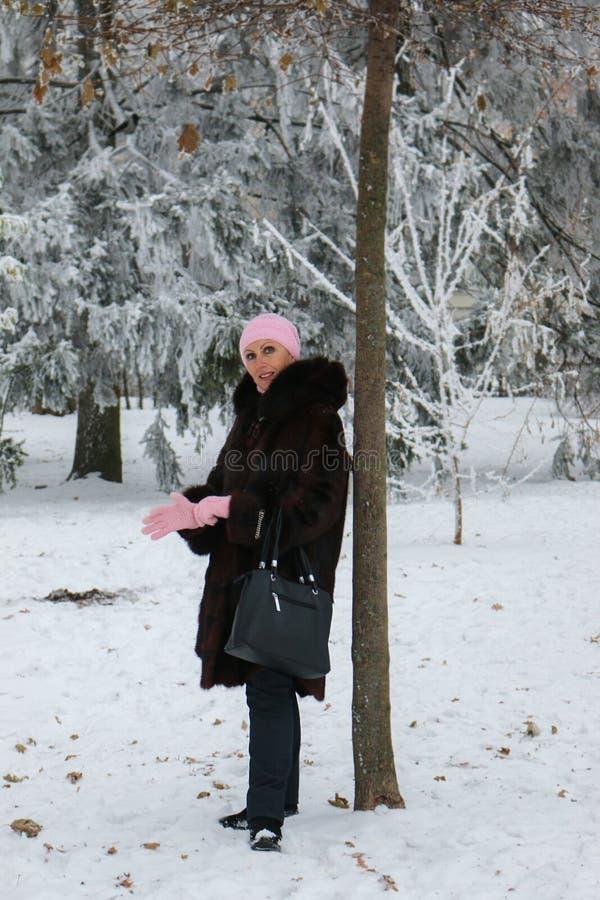 La donna sorridente in pelliccia sta restando vicino all'albero in parco fotografia stock