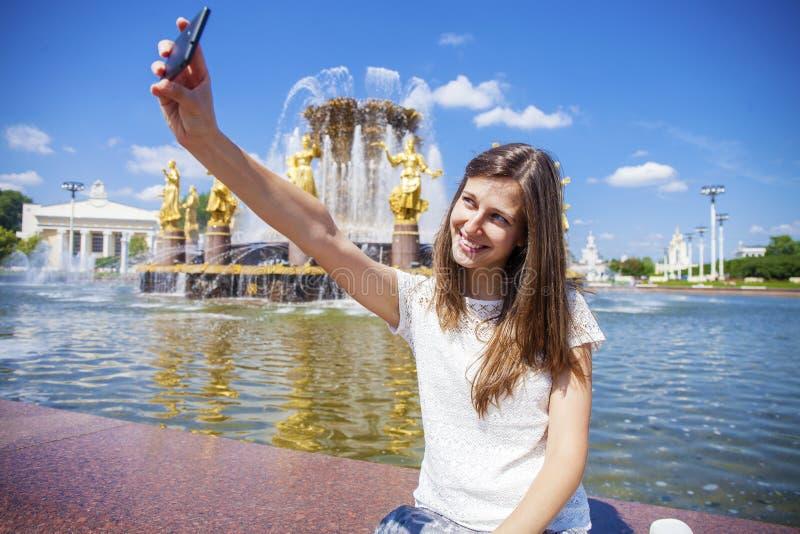 La donna sorridente prende un'immagine se stessa con uno smartphone Selfi immagine stock libera da diritti