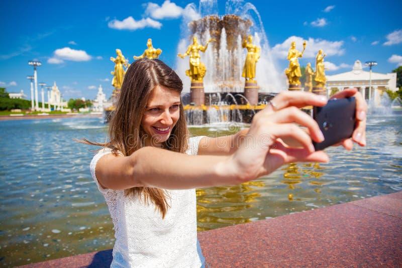 La donna sorridente prende un'immagine se stessa con uno smartphone Selfi fotografia stock libera da diritti