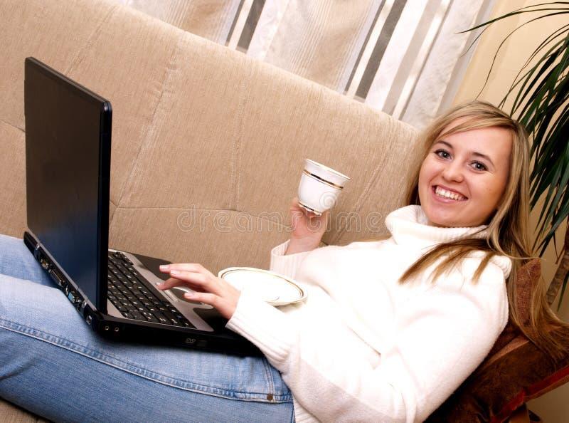 La donna sorridente si distende sul sofà. fotografia stock