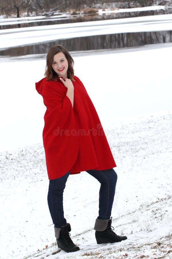 La donna sorridente sta all'aperto vicino ad una riva del fiume nevosa nel capo d'annata della lana immagini stock