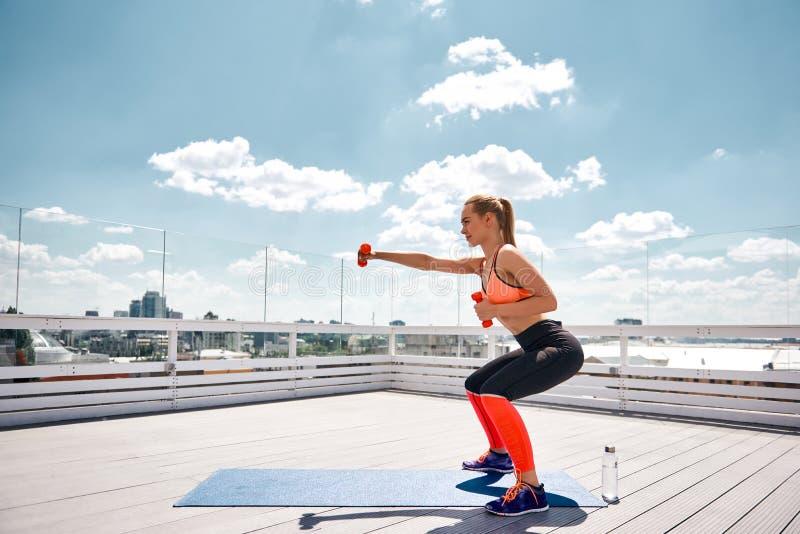 La donna sorridente sta esercitandosi con l'attrezzatura sull'alto terrazzo immagine stock libera da diritti