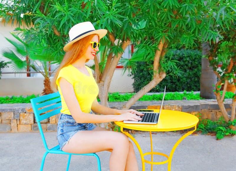 la donna sorridente sta lavorando facendo uso di un computer portatile si siede ad un caffè fotografia stock