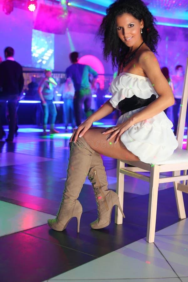 La donna sorridente in vestito si siede sulla presidenza in night-club fotografia stock libera da diritti