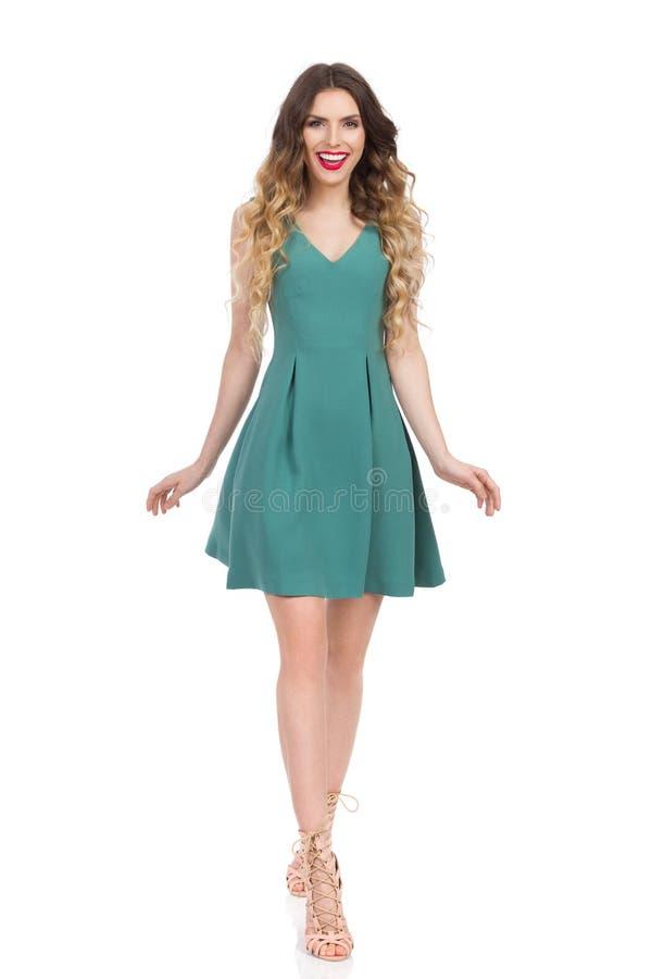 La donna sorridente in vestito verde sta camminando verso la macchina fotografica fotografia stock