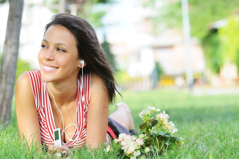 La donna in sosta verde, musica e si distende fotografia stock