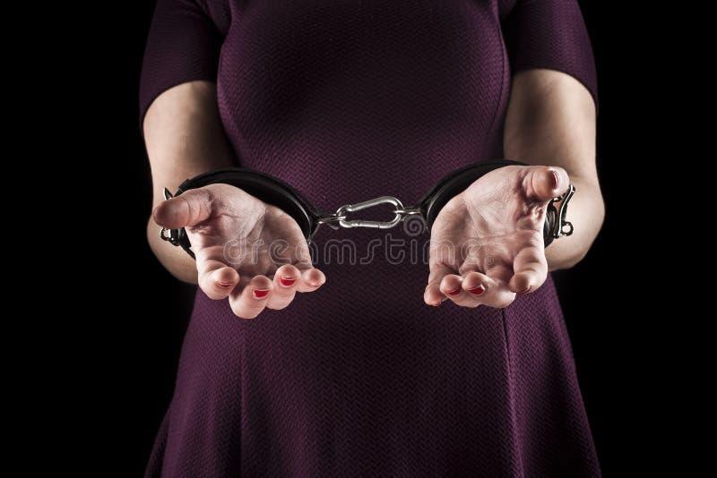 La donna sottomessa che porta un vestito porpora in cuoio ammanetta sopra immagini stock libere da diritti