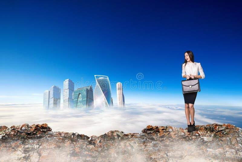 La donna spaventata di affari sta sull'orlo di catena montuosa fotografie stock