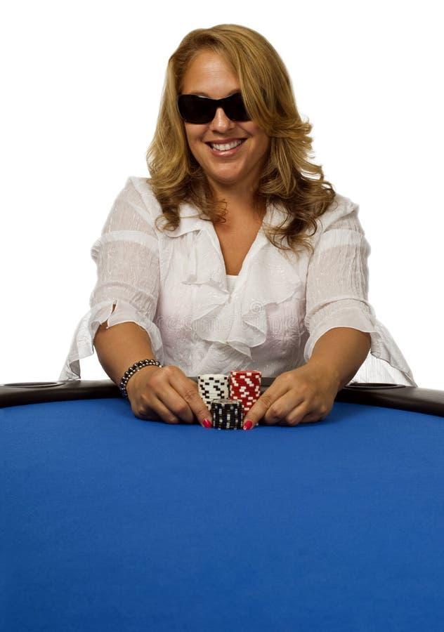 La donna spinge i chip di mazza sulla tabella blu immagine stock