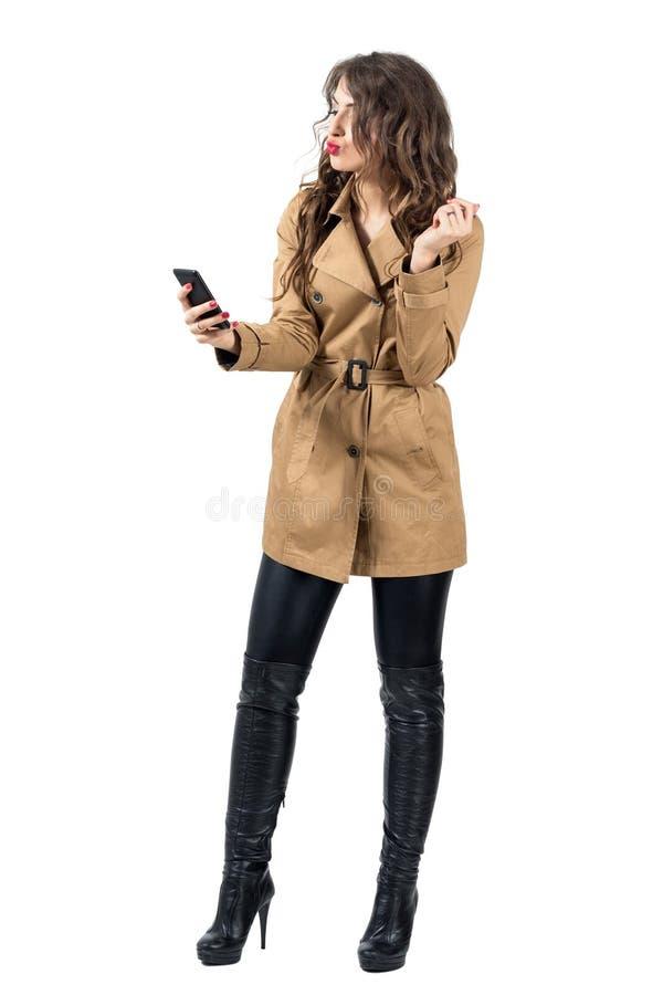 La donna splendida in autunno copre l'invio del bacio dell'aria ad una macchina fotografica del telefono cellulare immagine stock libera da diritti