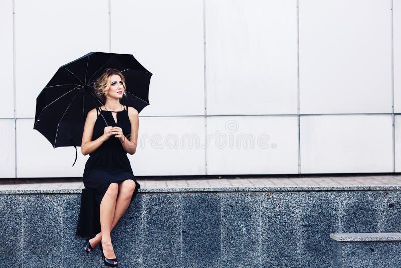 La donna splendida con un ombrello si siede sul parapetto e sulle attese immagini stock