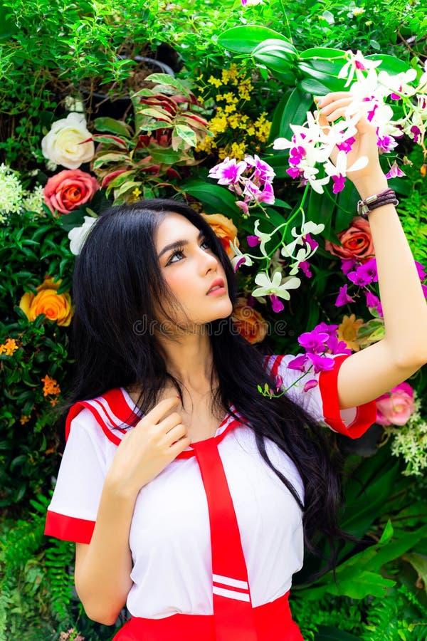 La donna splendida esamina i bei fiori e lo tiene ad un parco fotografia stock libera da diritti