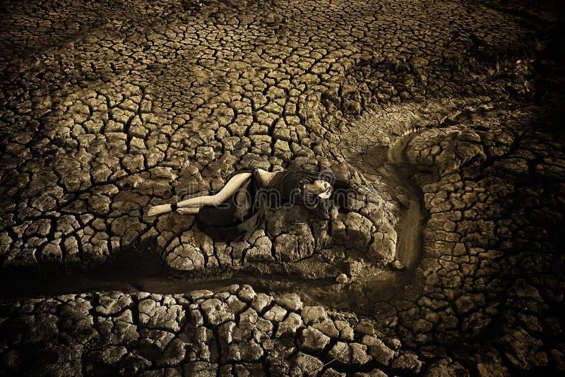 La donna sporca triste è al deserto incrinato della terra fotografia stock libera da diritti