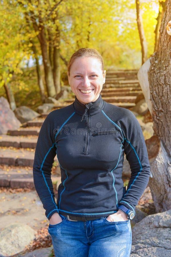 La donna sportiva allegra sta ridendo nel parco di autunno fotografia stock libera da diritti