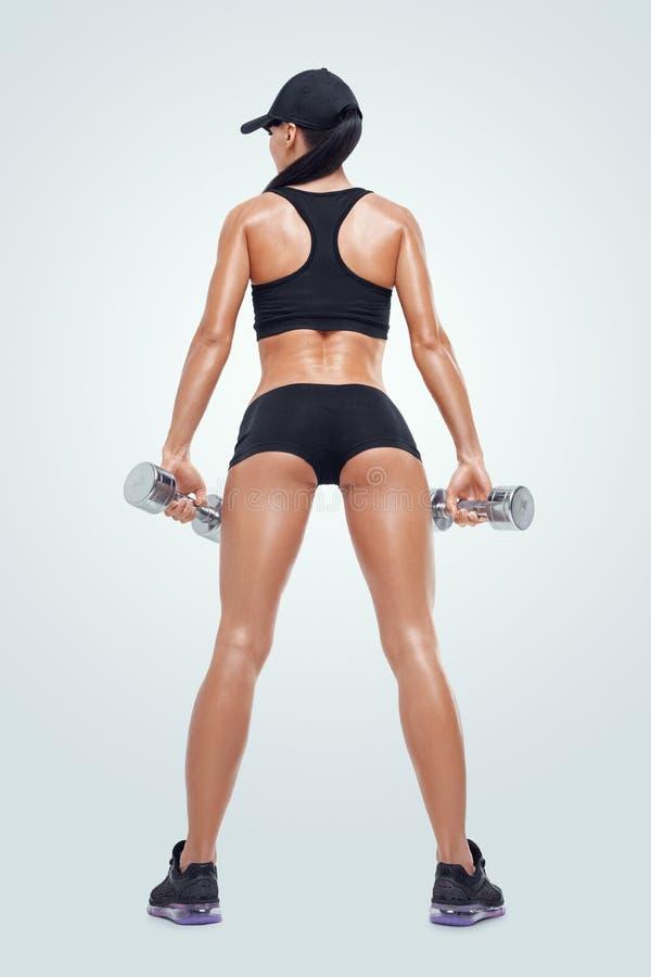 La donna sportiva di forma fisica nell'addestramento che pompa su muscles con le teste di legno fotografie stock libere da diritti