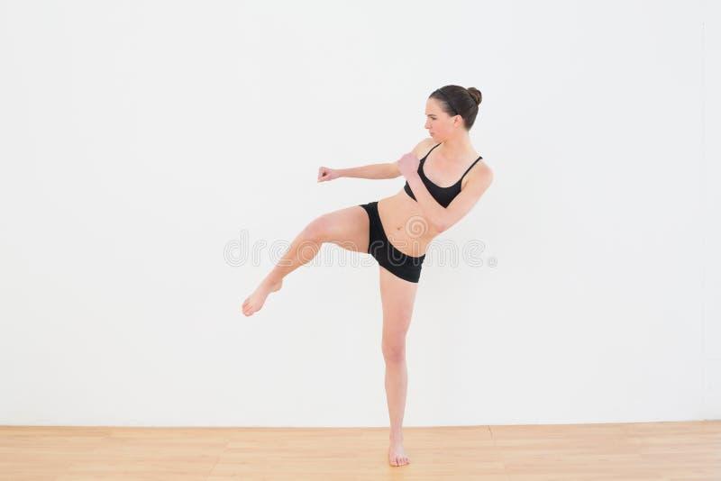 La donna sportiva di misura che esegue un'aria dà dei calci dentro allo studio di forma fisica immagine stock