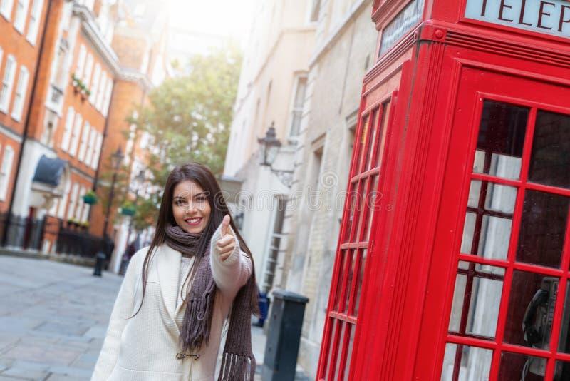 La donna sta accanto ad una cabina telefonica rossa a Londra e mostra i pollici sul segno immagine stock