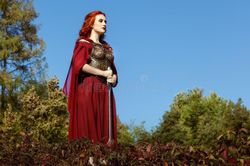 La donna sta alta, una spada in sue mani fotografia stock