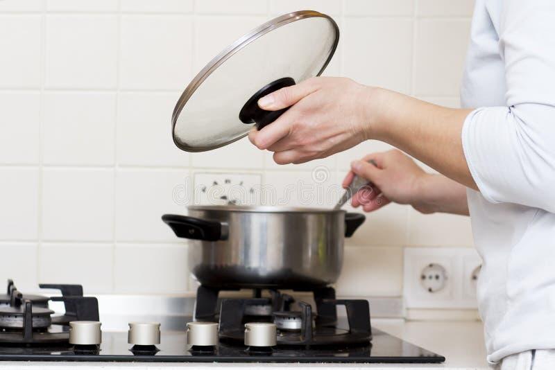 La donna sta cucinando la minestra in cucina la casalinga prepara l'alimento a casa la donna caucasica tiene il coperchio dalla c fotografie stock libere da diritti