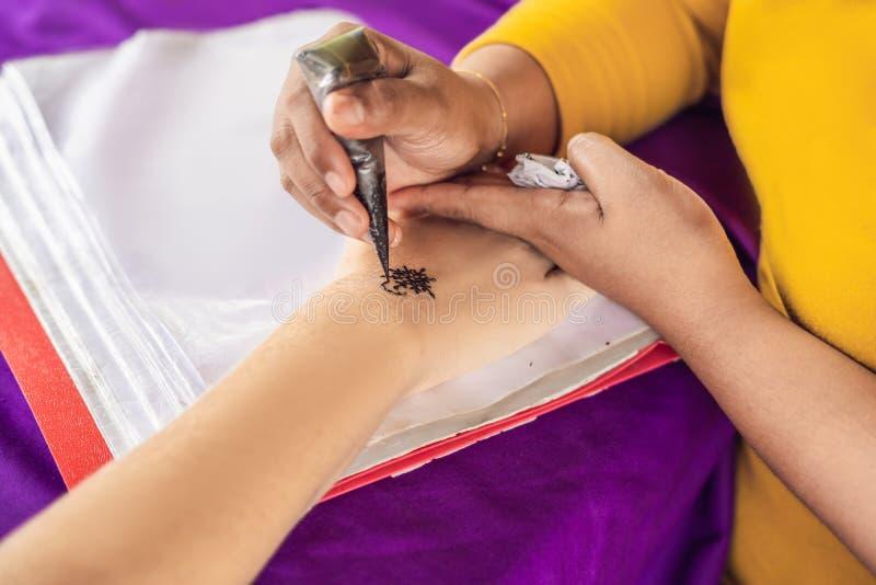 La donna sta disegnando a disposizione Attinga il pictur indiano di mehendi della mano fotografia stock libera da diritti