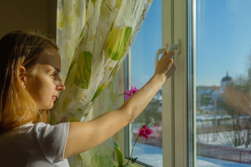 La donna sta esaminando il paesaggio nevoso il giorno gelido soleggiato fotografia stock libera da diritti