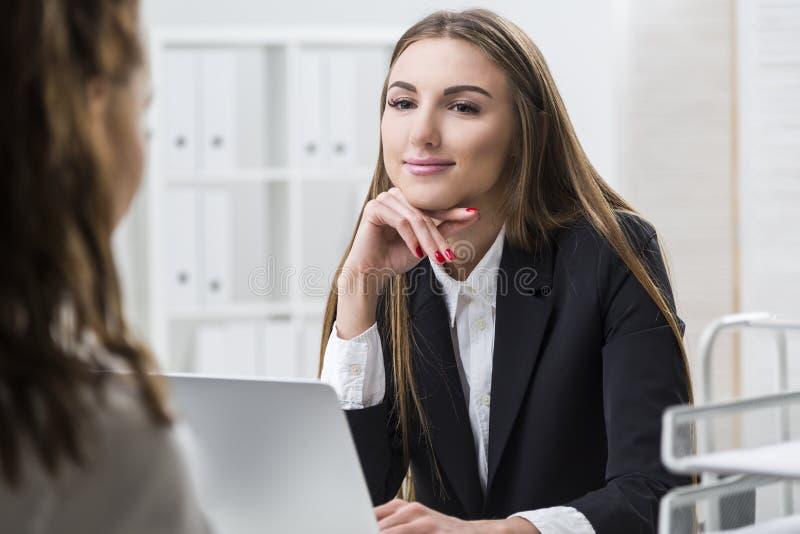La donna sta esaminando il suo collega con amore immagine stock libera da diritti