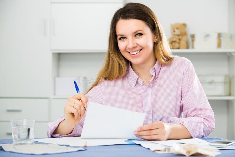 La donna sta firmando l'accordo finanziario proficuo fotografia stock
